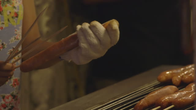 CU Shot of gloved hands of woman skewering suasages and putting them on street grill / Taipei, Taiwan