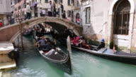 MS Shot of gondolas ferry passing down under bridge, San Marco / Venice, Veneto, Italy