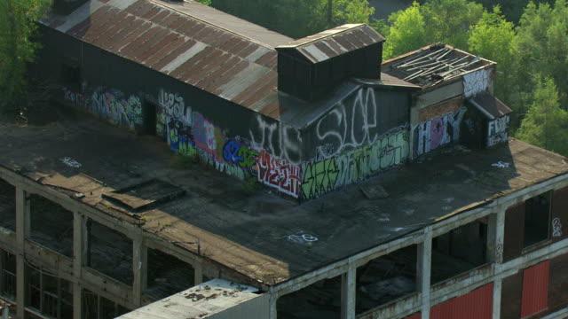MS AERIAL Shot of  graffiti at abandoned Packard Automotive Plant / Detroit, Michigan, United States