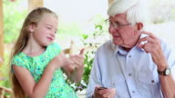 MS Shot of granddaughter and grandfather listening to ipod together / Lamy, New Mexico, United States