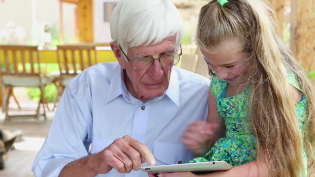 MS Shot of granddaugther and grandfather looking at ipad together / Lamy, New Mexico, United States