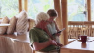 MS Shot of grandfather and granddaughter looking at tablet / Ubud, Bali, Indonesia