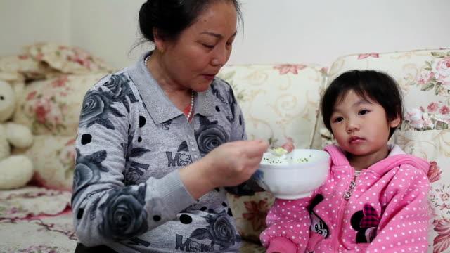 MS PAN Shot of Grandma feeding granddaughter with spoon and granddaughter watching TV / Xian, China