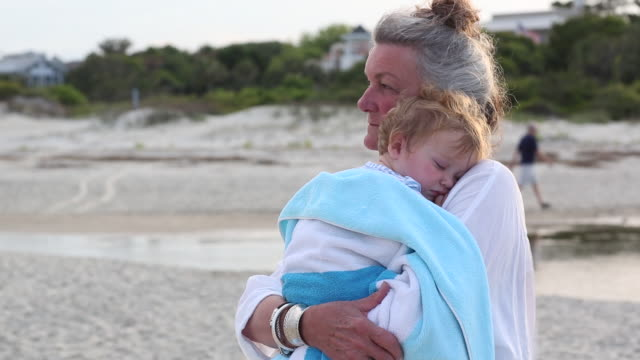 MS Shot of grandmother holding her baby grandson and looking out at ocean / St Simon's Island, Georgia, United States