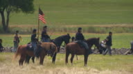 MS TU Shot of Grass to four soldiers on horseback carrying Round Pattern flag during Battle of Gettysburg / Gettysburg, Virginia, United States