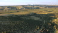 MS AERIAL TU LA Shot of Grass to reveal hills of Killpecker Sand Dunes / Wyoming, United States
