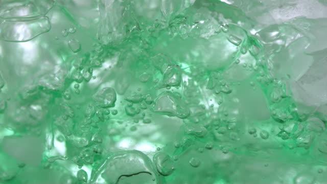 ECU SLO MO Shot of Green liquid pour into glass of ice / Toronto, Ontario, Canada