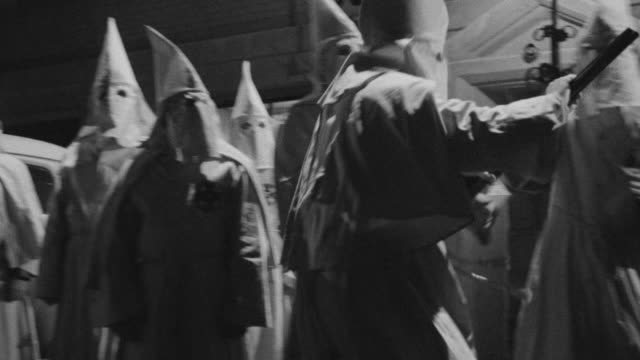 MS Shot of Group of hooded clansmen in front of county jail entrance