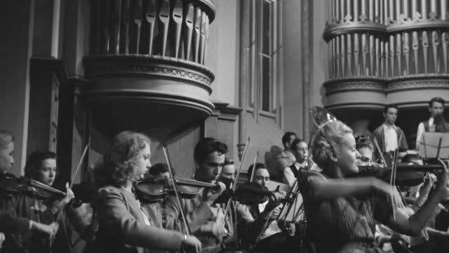 MS PAN Shot of group playing violin in music hall