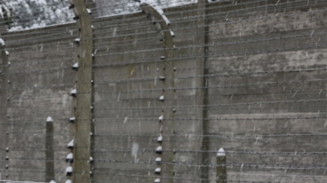 CU PAN Shot of 'Halt' sign at Auschwitz with snow rain / Auschwitz-Birkenau, Krakow, Poland