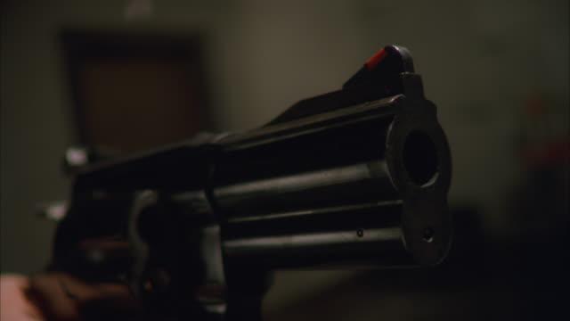 CU Shot of hand holding gun and Firing