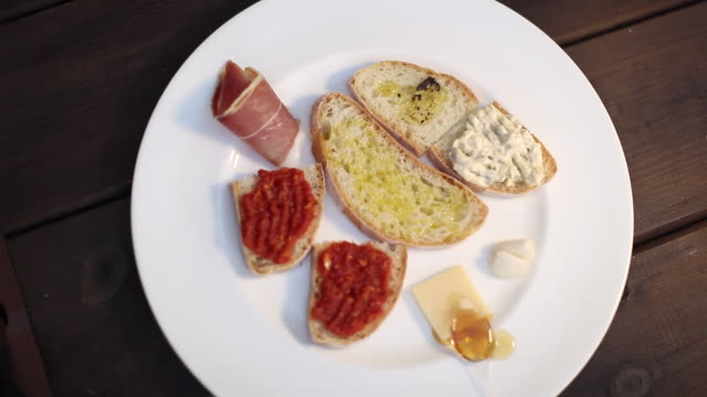 CU R/F Shot of hand showing dishes of bruschettas / Castellina In Chianti, Tuscany, Italy
