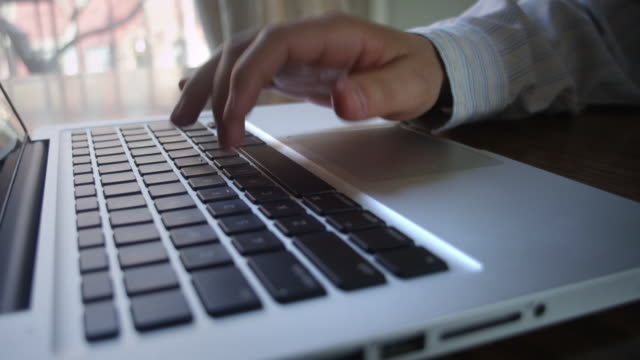 CU Shot of hand using track pad mouse and typing on laptop / New York, United States