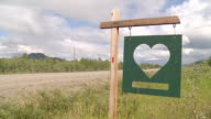 CU Shot of Handmade loveheart cut out roadside sign with car passing on Haines Highway near Kluane National Park and Reserve / Yukon, Canada