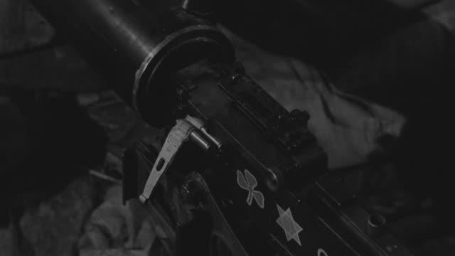 ECU Shot of hands loading belt of bullets into machine gun