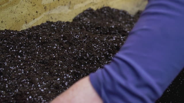 CU PAN SLO MO Shot of hands mixing soil for planting / Chatham, Michigan, United States