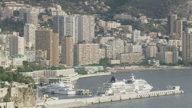 MS AERIAL ZO Shot of harbor along with tall buildings near coast / Monaco, France