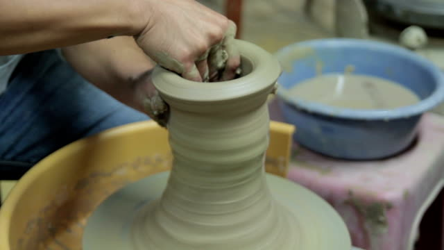 Shot of holding clay and making pottery shape with hands and pottery wheel