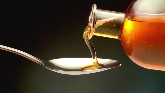 CU Shot of honey pouring on spoon / Spain