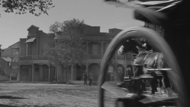 MS Shot of Horse and carriage ride through western town