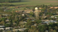 MS AERIAL Shot of houses and water tower with trees, buildings / Franklin, Louisiana, United States