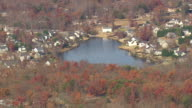 MS AERIAL TD Shot of houses surrounded by autumn color trees with small lake / South Carolina, United States