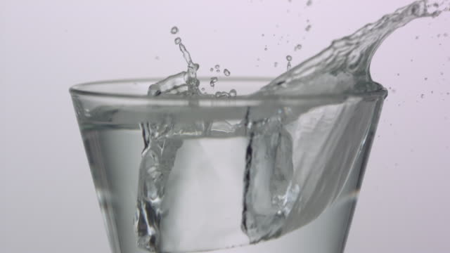 ECU SLO MO Shot of Ice falling into glass / Toronto, Ontario, Canada