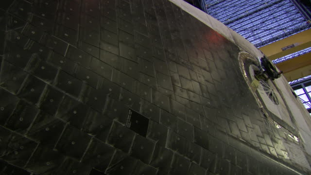 CU PAN Shot of insulating black tiles on exterior of Space Shuttle Discovery inside Vehicle Assembly Building at Kennedy Space Center / Cape Canaveral, Florida, United States