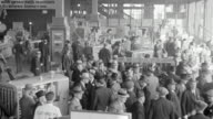 MS Shot of interior of Catepillar tractor factory as tractors are being inspected by crowd of men.