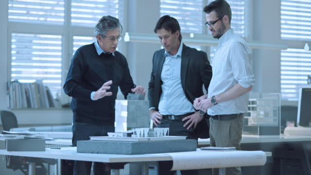 LD shot of investor discussing the design plans with architects