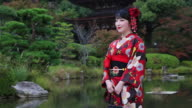 CU Shot of Japanese woman smiling with kimono standing in front of Japanese Traditional garden / Yamaguchi, Yamaguchi Prefecture, Japan