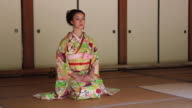 MS Shot of Japanese woman with kimono bowing, Japanese style sitting on Tatami floor / Yamaguchi, Yamaguchi Prefecture, Japan
