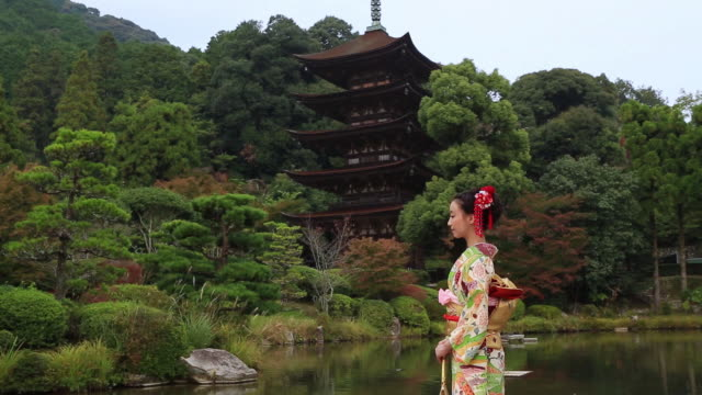 MS Shot of Japanese woman with kimono standing in front of Japanese Traditional garden / Yamaguchi, Yamaguchi Prefecture, Japan