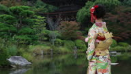 CU PAN Shot of Japanese woman with kimono standing in front of Japanese Traditional garden / Yamaguchi, Yamaguchi Prefecture, Japan