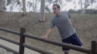 MS PAN Shot of Jogger stretches and exits frame / Los Angeles, California, United States