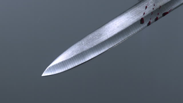 CU Shot of Knife with Blood Dripping from Blade against Grey Background / Calvados, Normandy, France