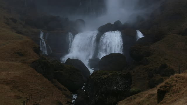 MS TU Shot of Krossarfoss Falls and stream which large quantities of water falling in to basin of Falls from top of cliff / Iceland