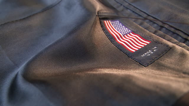 CU Shot of label being sewn onto inside of suit jacket