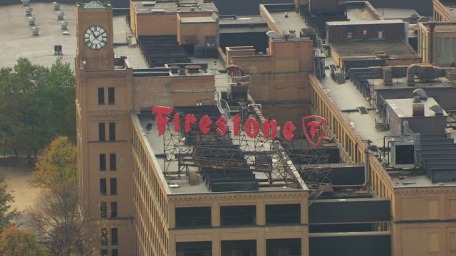 MS ZI AERIAL Shot of large Firestone sign on top of old Firestone factory building / Akron, Ohio, United States