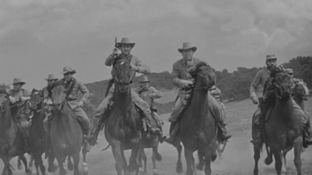 MS POV Shot of large group of men riding through open field on horseback toward