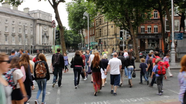 MS Shot of Large group of pedestrians crossing street / Dublin, Dublin Region, Ireland