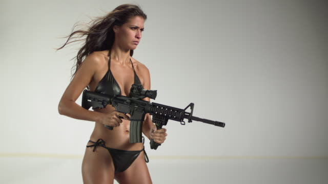 MS SLO MO Shot of Latin middle eastern female firing MR27 machine gun, bullets coming out of side / Studio, New York, United States