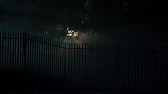 MS Shot of light shining through trees and metallic spikey fence at night / various, United Kingdom