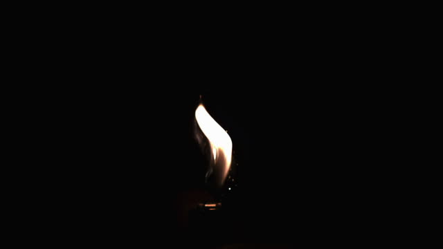 MS SLO MO Shot of lighter flame and sparks in dark / Vieux Pont, Normandy, France