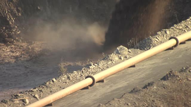 CU AERIAL TU Shot of liquid rock and pull back to bridge unloaded dumping liquid rock into pile at Hull Rust Mahoning Mine / Chisholm, Minnesota, United States