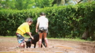 MS Shot of little boy and little girl are ankle high in mud puddle and little boy pulling his foot out of his boots then dog comes into puddle and little boy pushes dog into mud bath / Montezuma, Punteranes, Costa Rica