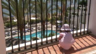 MS Shot of little girl looking near swimming pool through railings / Marbella, Andalusia, Spain