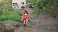 WS Shot of little girl running while holding stick for little black puppy following with cabina, ocean, laundry line and palm trees / Montezuma, Punteranes, Costa Rica