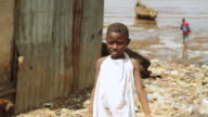 MS Shot of little girl standing near beach and boats in sea / Freetown, Sierra Leone