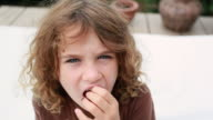 CU Shot of little girl twisting her loose front tooth and then pulling it out / Montezuma, Punteranes, Costa Rica